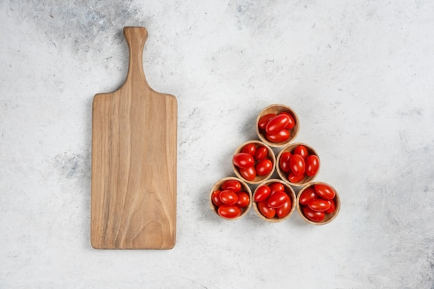 Fresh red cherry tomatoes in wooden bowls.