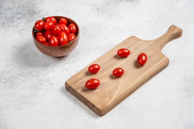 Pomodorini rossi freschi su un tagliere di legno