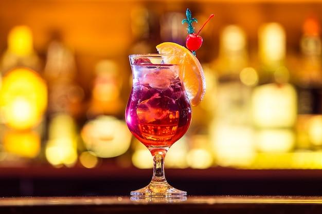 バーに立っている氷とオレンジのスライスと新鮮な赤いカクテル。アルコール飲料(閉じる)