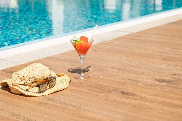 ガラスの氷、ビーチ帽子、スイミングプールのサングラスと新鮮な赤いカクテル。贅沢な休暇のトロピカルジュース。コンセプト夏休みと旅行。高品質の写真