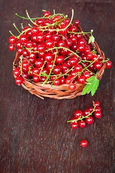 Fresh red currant berries in a wicker bowl in the old wooden table
