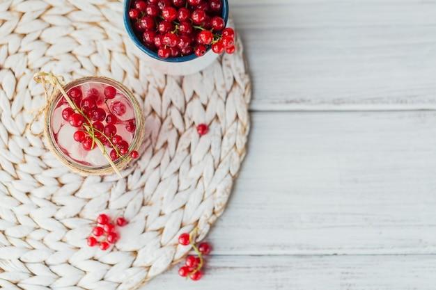 ガラスの瓶に新鮮な赤スグリのカクテル。テキスト用のコピースペースを備えた白い木製のモックアップに赤スグリと角氷を添えた夏のピンクのカクテル。