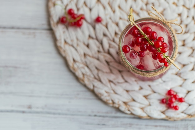 ガラスの瓶に新鮮な赤スグリのカクテル。白い木製のテーブルに赤スグリと角氷と夏のピンクのカクテル