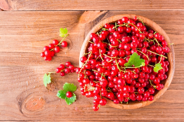 Fresh red currant in a wooden plate on a table