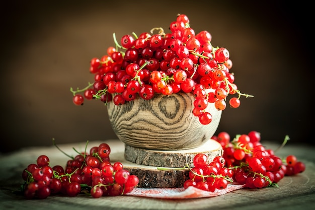 Fresh red currants in plate on dark rustic wooden table