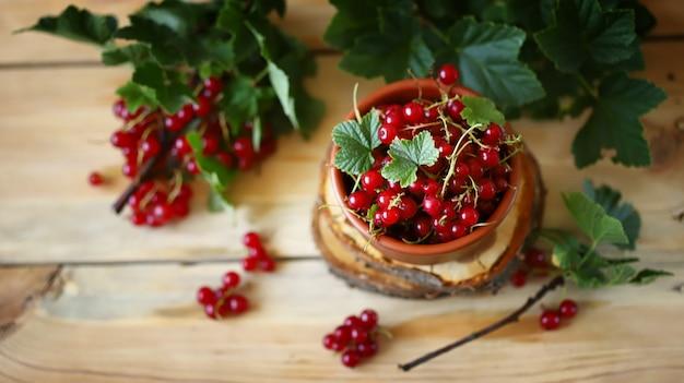 木製の背景の葉と新鮮な赤スグリ