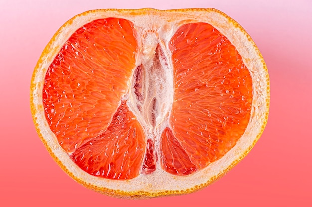 Fresh red cut grapefruit on pink surface. female health concept. fruit as symbol of vagina. close up.