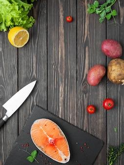 新鮮な赤い魚のステーキ、サーモン、ダークウッドのテーブル