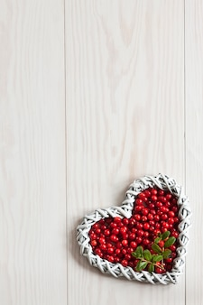 Fresh red forest berries in the shape of heart