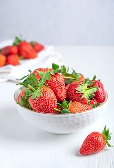 Свежая красная садовая клубника с сочной текстурой и сладостью подается в миске на белом деревянном столе