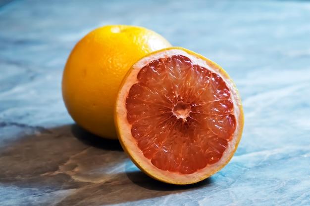 Fresh red grapefruit slice on table