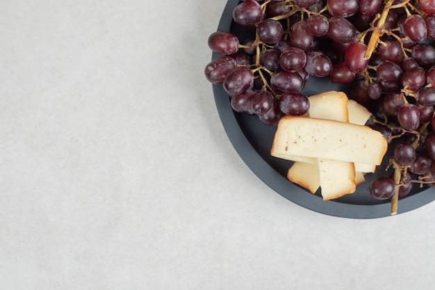 어두운 보드에 신선한 붉은 포도와 치즈 조각