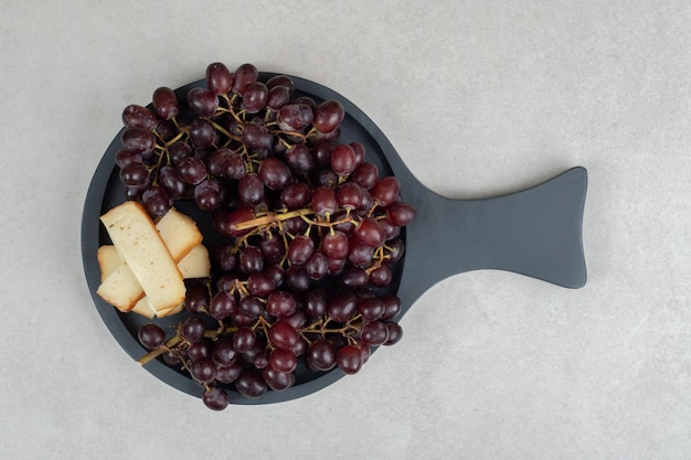 Fresh red grapes and cheese slices on dark board