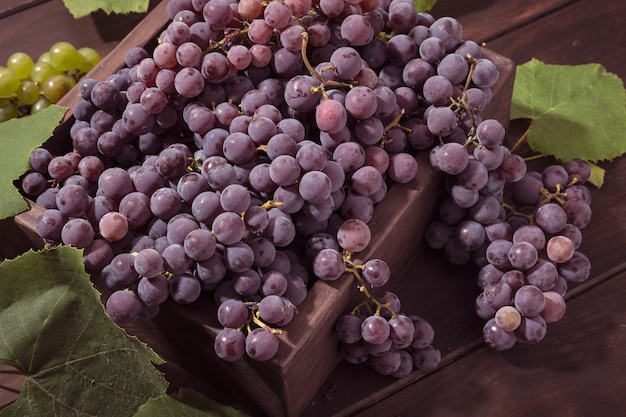 Fresh red grapes in crate on wooden table