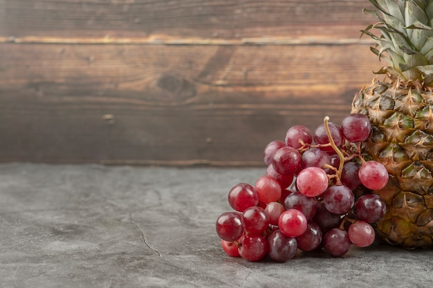 Fresh red grapes with ripe pineapple on marble surface.