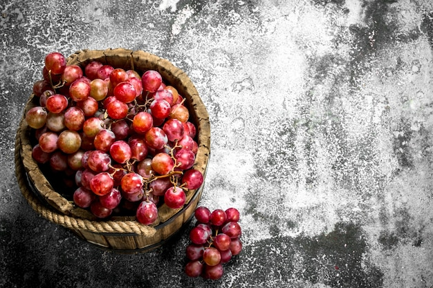 Fresh red grapes in a wooden bucket.