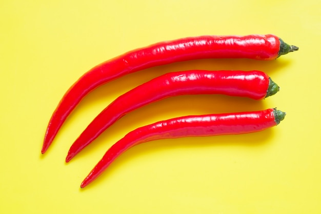 Fresh red hot chili pepper on yellow background.
