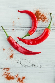Fresh red hot chili peppers and dried paprika on a white wooden table