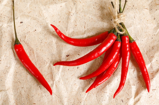 Fresh red hot peppers on craft paper