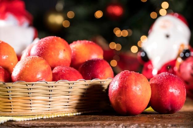 나무 그릇과 흐리게 크리스마스 장식에 신선한 붉은 천도 복숭아