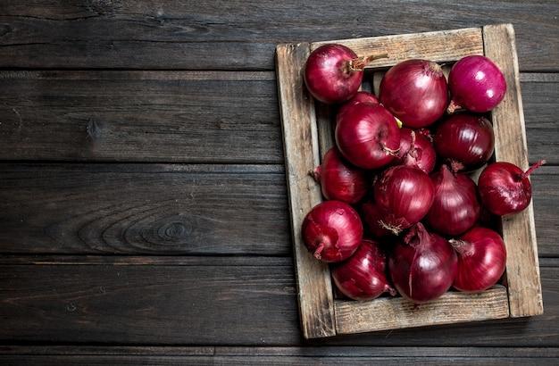 トレイに新鮮な赤玉ねぎ。木製のテーブルの上