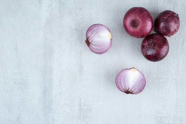 Fresh red onions on stone surface.