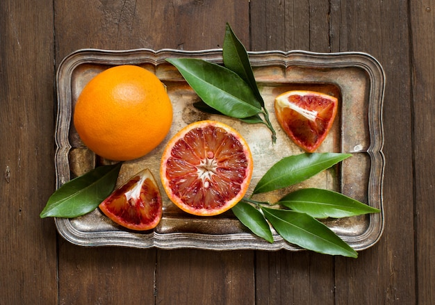 Fresh red oranges on a tray on a wooden table