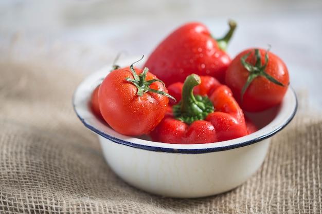 Свежий красный перец и помидоры в белой металлической миске здоровое фото высокого качества