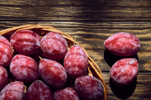 Fresh red plum on dark wooden table, shallow depth of field