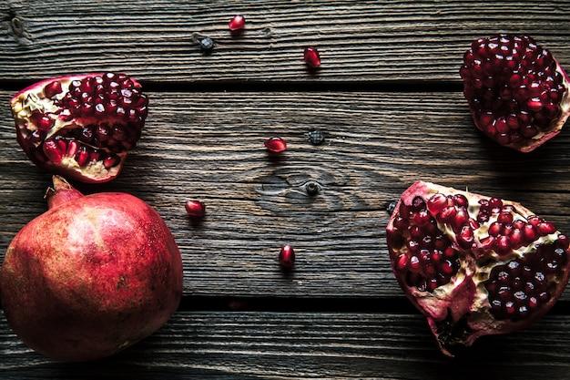Свежий красный гранат и грейпфрут на деревянных фоне. гранат в тарелке на деревянном фоне. гранат на текстурированном фоне дерева
