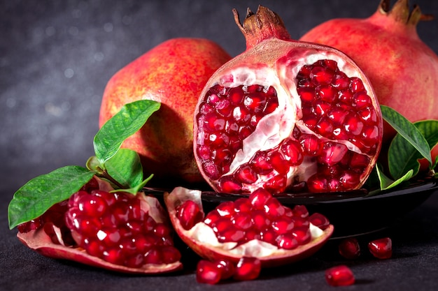 Fresh red pomegranate and seed  with leaves over black stone background
