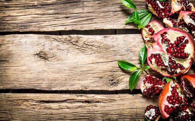葉と新鮮な赤いザクロ。木製の背景に。テキスト用の空き容量。上面図