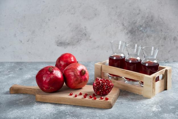 주스와 나무 보드에 신선한 빨간 석류입니다.