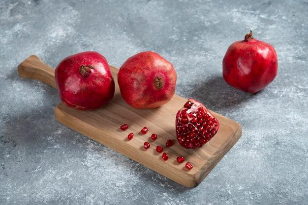 목 판에 신선한 빨간 석류입니다.