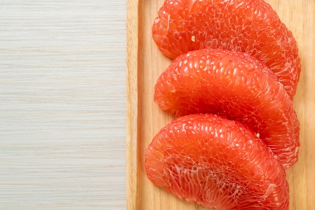 プレート上の新鮮な赤いザボンフルーツまたはグレープフルーツ