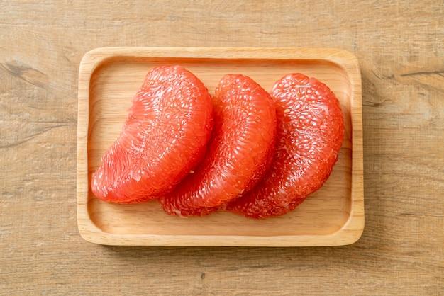 皿に新鮮な赤いザボンフルーツまたはグレープフルーツ
