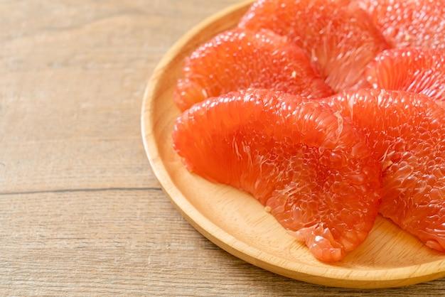 皿に新鮮な赤いザボンフルーツまたはグレープフルーツ Premium写真