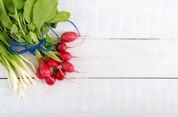 신선한 빨간 무와 흰색 나무 바탕에 녹색 젊은 양파. 무와 건강 한 다이어트. 가벼운 봄 야채 샐러드 재료. 비문을위한 여유 공간.