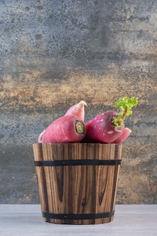 Свежий красный редис в деревянном ведре. фото высокого качества