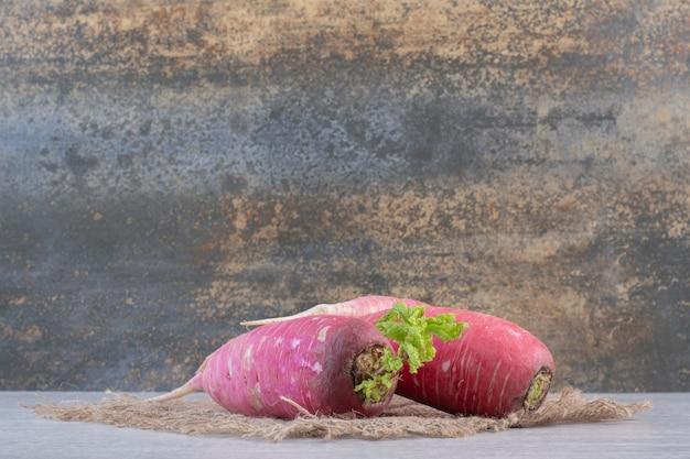 Свежий красный редис на мраморной предпосылке с мешковиной. фото высокого качества