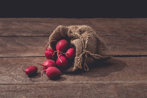 Fresh red radishes on wooden table