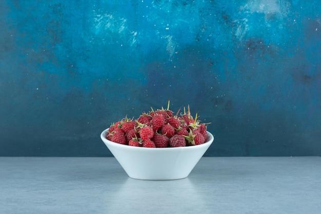 하얀 그릇에 신선한 빨간 라스베리입니다.