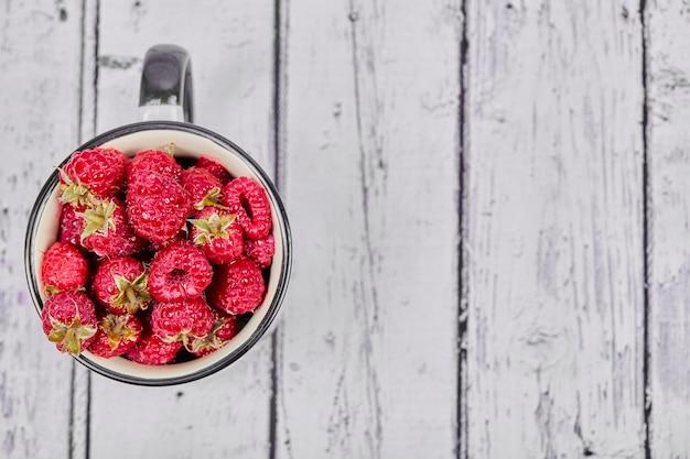 木製のテーブルの上のマグカップに新鮮な赤いラズベリー。
