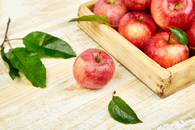 木製の箱に新鮮な赤い熟したリンゴの果実。