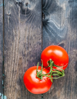 Fresh red ripe tomatoes on a branch on a wooden background