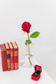 Fresh red rose in vase near present box with ring and books on table