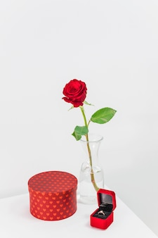 Fresh red rose in vase near present and jewellery box with ring on table