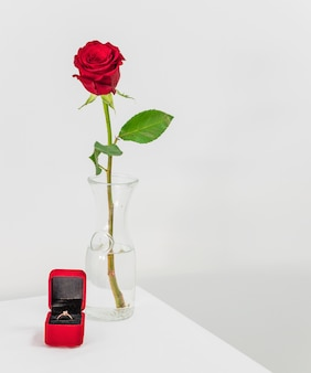Fresh red rose in vase and present box with ring on table