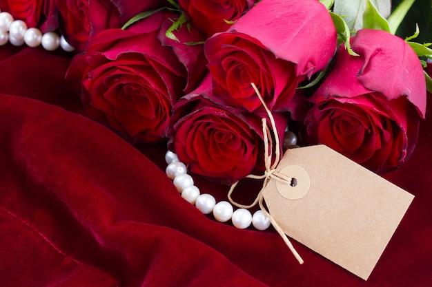 空のタグと緋色のベルベットの背景に新鮮な赤いバラ
