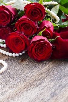 Свежие красные розы с жемчужными украшениями на деревянных фоне